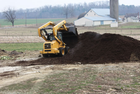Turning over brown gold compost. We work hard to reduce our fertilizer use on your veggies.